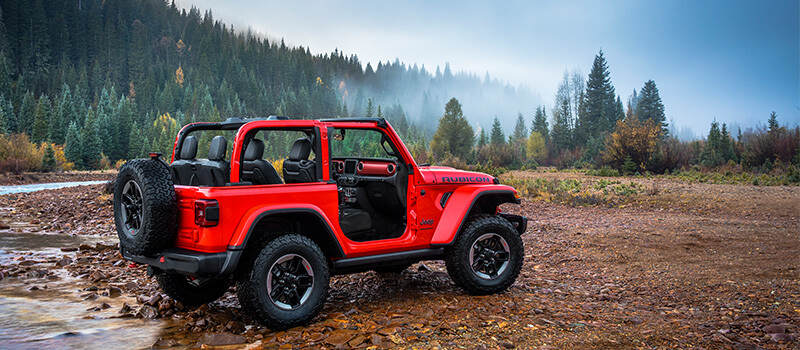 2 Door Jeep Wrangler Rubicon parked outside by a river with the doors and roof removed